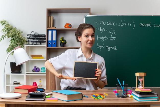 Feliz joven profesora de matemáticas sentada en un escritorio con útiles escolares sosteniendo y apuntando a la mini pizarra mirando al frente en el aula
