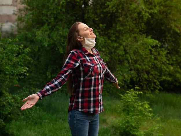 Feliz joven se quita una máscara médica y respira aire fresco en la naturaleza
