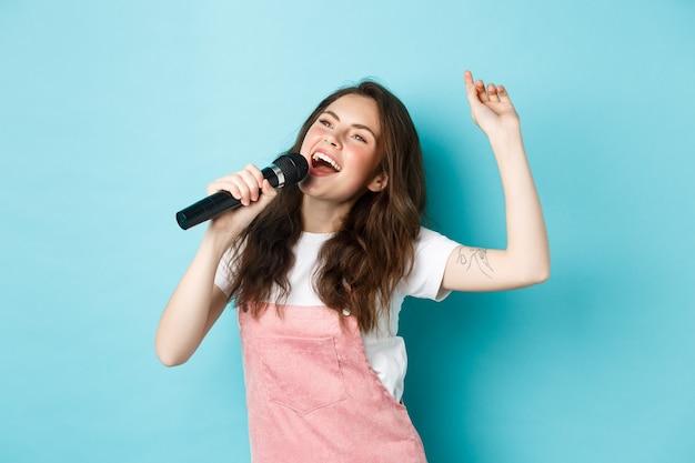 Feliz joven realizar la canción, cantante sosteniendo el micrófono, bailando y cantando en el karaoke, de pie sobre fondo azul.