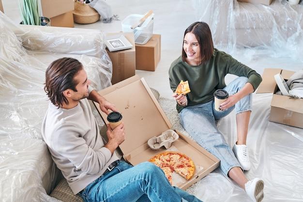 Feliz joven con una rebanada de pizza y un vaso de café hablando con su marido por el almuerzo en el piso de la sala de estar