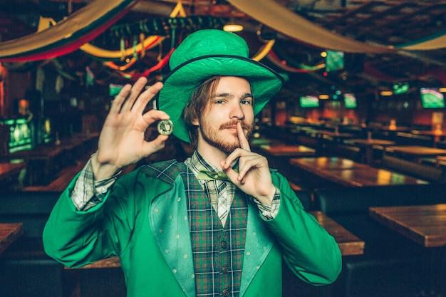 Feliz joven rico en traje de san patricio de pie en el pub y sostener la moneda de oro. tiene el dedo cerca de la boca. chico mira. el está solo.