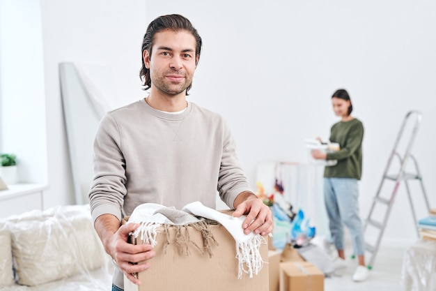 Feliz joven en ropa casual mirándote mientras desempaqueta cajas y su esposa con contenedor
