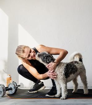 Feliz joven rubia acariciando a su perro en el gimnasio en casa