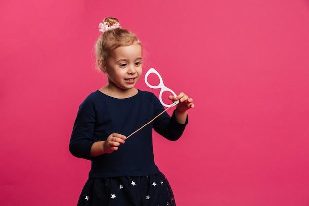 Feliz joven rubia jugando con lentes de papel sobre pared rosa