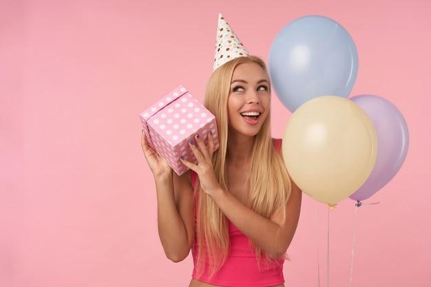 Feliz joven rubia de pelo largo sosteniendo una caja envuelta para regalo y preguntándose qué hay dentro, se regocija en una agradable fiesta junto con amigos, de pie sobre un fondo rosa y globos de aire multicolores