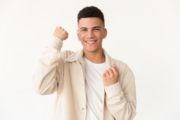 Feliz joven sacudiendo puños
