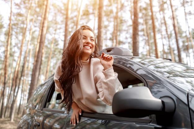 Feliz joven salió de la ventanilla de un automóvil. viajando en coche por el bosque. viaje de campo. vacaciones en coche
