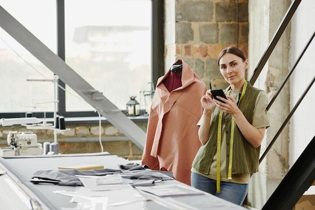 Feliz joven sastre y propietario de un estudio de moda tomando nuevos pedidos de los clientes mientras está de pie junto a la mesa con bocetos y ropa sin terminar