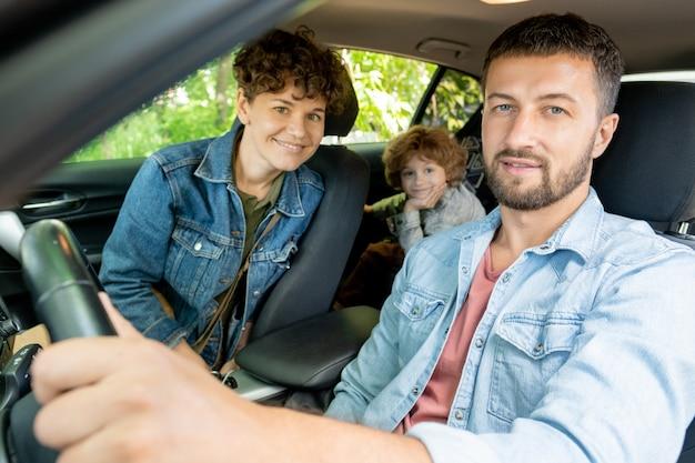 Feliz joven sentado al volante en el coche con una bonita esposa y su lindo hijo en el asiento trasero mirándote