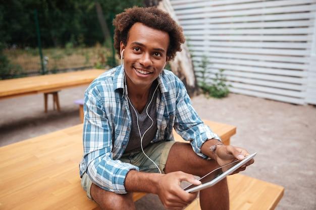 Feliz joven sentado y escuchando música desde la tableta
