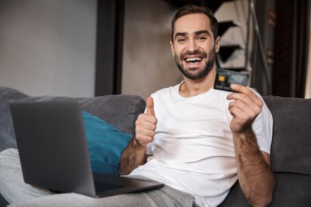 Feliz joven sentado en un sofá, usando una computadora portátil, celebrando, mostrando una tarjeta de crédito plástica