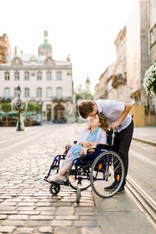Feliz joven en silla de ruedas y su esposo besando su frente, caminando al aire libre en la ciudad vieja