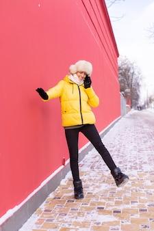 Feliz joven sobre un fondo de una pared roja en ropa de abrigo en un día soleado de invierno sonriendo y hablando por teléfono en una acera nevada de la ciudad