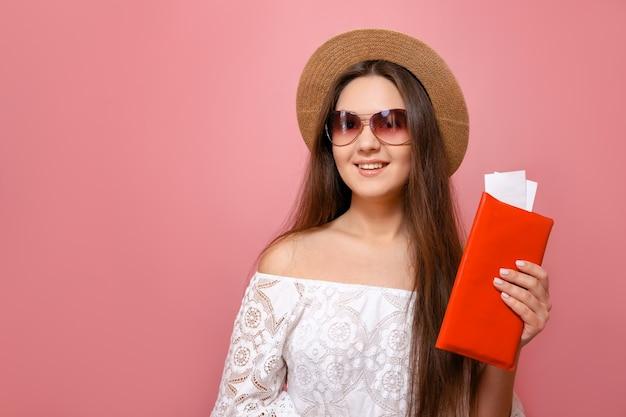 Feliz joven con sombrero con billetes de avión sobre fondo rosa