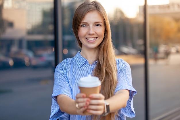 Feliz joven sonriendo a la cámara ofreciendo café en vaso de papel desechable
