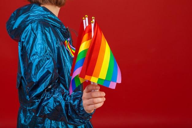 Feliz joven sonriente con su mano sosteniendo la bandera del arco iris colorido lgbt