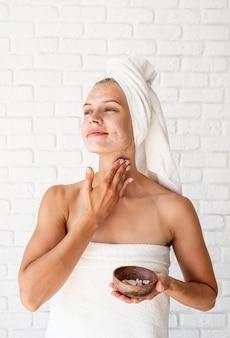 Feliz joven sonriente en toallas de baño blancas aplicando exfoliante en la cara y el cuello