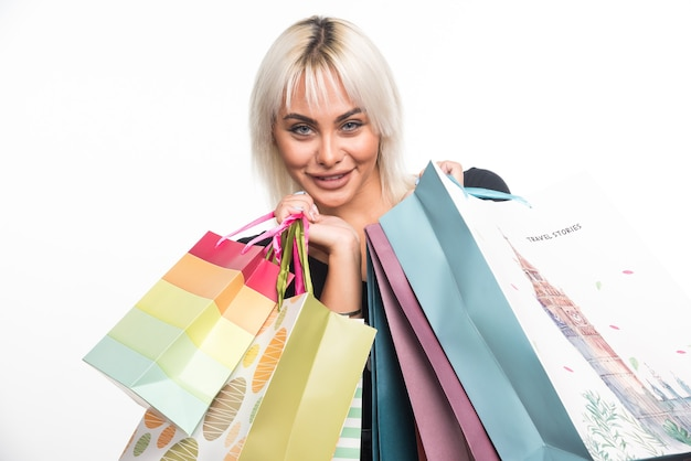 Feliz joven sosteniendo bolsas de la compra sobre fondo blanco. foto de alta calidad