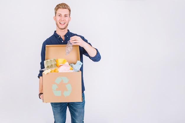 Feliz joven sosteniendo la caja de cartón llena de basura con el icono de reciclaje