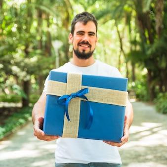 Feliz joven sosteniendo la caja de regalo azul