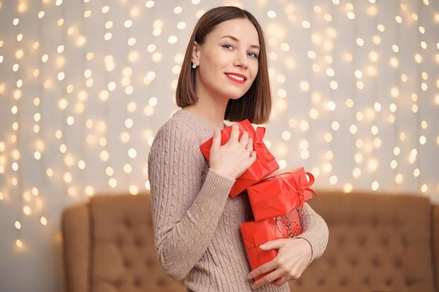 Feliz joven sosteniendo muchas cajas presentes con árbol de navidad y luces