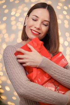Feliz joven sosteniendo muchas cajas presentes con luces