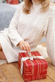 Feliz joven sosteniendo un presente rodeado de cajas de regalo se sienta con las piernas cruzadas en un sofá de camello. regalo de navidad en manos de una niña, primer plano.