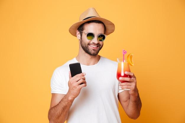 Feliz joven sosteniendo teléfono móvil y cóctel