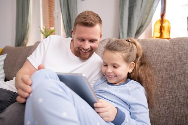 Feliz joven y su linda hijita con touchpad riendo mientras ve una película en línea y lo discute en el entorno doméstico