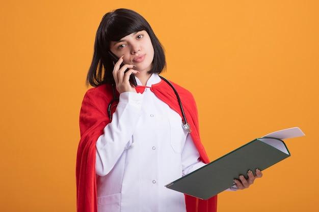 Feliz joven superhéroe con estetoscopio con bata médica y manto sosteniendo portapapeles habla por teléfono aislado en la pared naranja