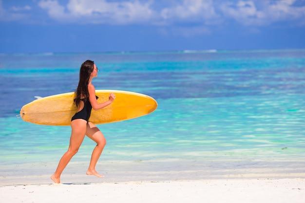 Feliz joven surf mujer corriendo en la playa con una tabla de surf