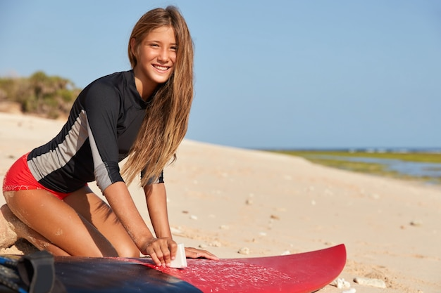 Feliz joven surfista experimentado viste bikini rojo, tiene la piel bronceada, cuerpo sano, encera la tabla de surf