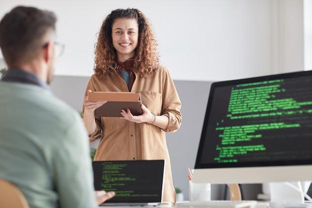 Feliz joven con tableta digital consultando con su colega mientras él trabaja en la computadora con software