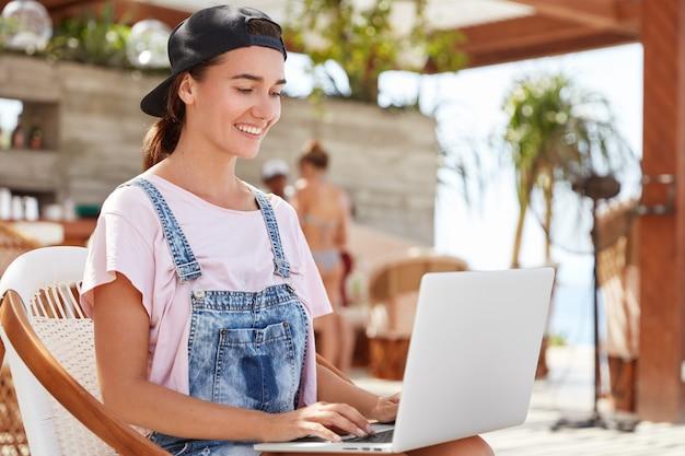 Feliz joven tiene expresión positiva funciona de forma remota en la computadora portátil