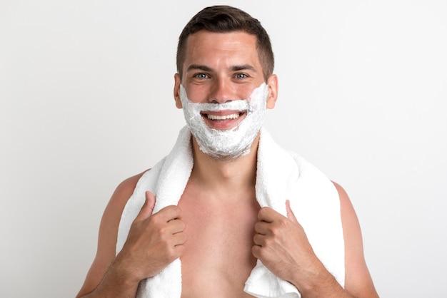 Feliz joven con toalla aplicada espuma de afeitar en su rostro de pie contra la pared
