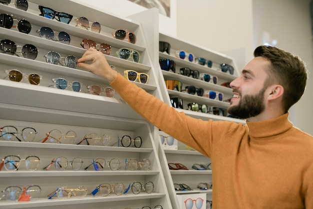 Feliz joven tomando un par de anteojos elegantes mientras está de pie junto a la pantalla con surtido de gafas en la tienda de óptica