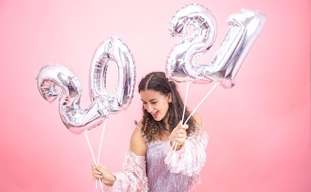 Feliz joven en traje de fiesta posando sosteniendo globos plateados para el concepto de año nuevo