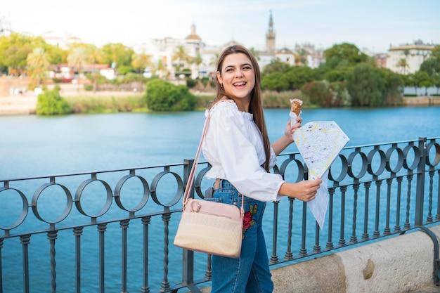 Feliz joven turista tomando un helado y usando un mapa caminando por el río en sevilla españa
