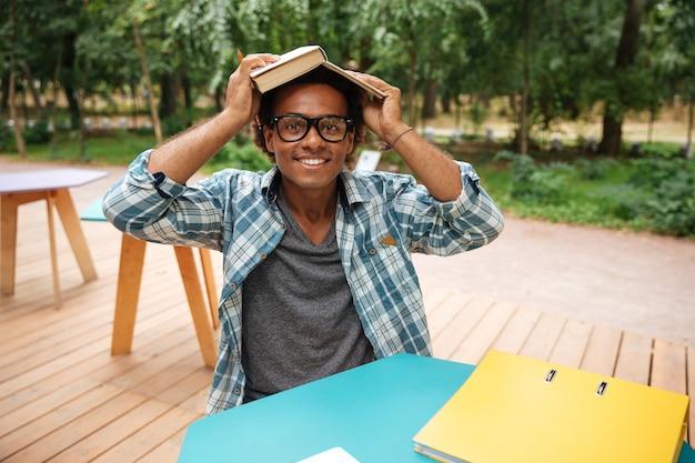 Feliz joven en vasos estudiando y divirtiéndose en la cafetería al aire libre
