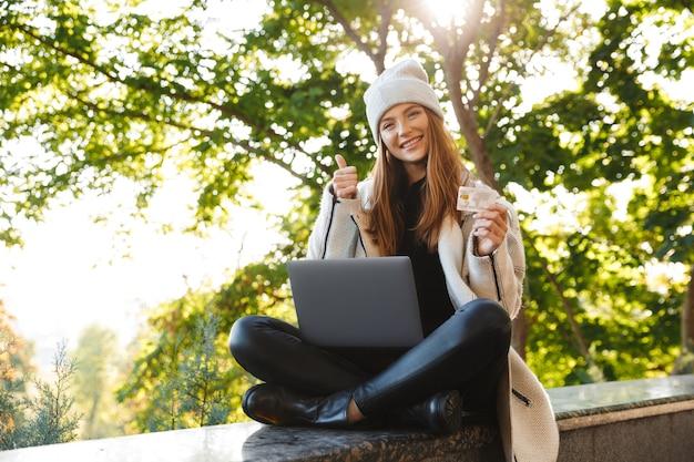 Feliz joven vestida con abrigo y sombrero de otoño sentado al aire libre, usando una computadora portátil, mostrando una tarjeta de crédito de plástico
