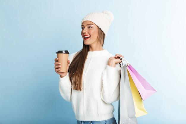 Feliz joven vistiendo suéter, llevando bolsas de la compra, tomando café