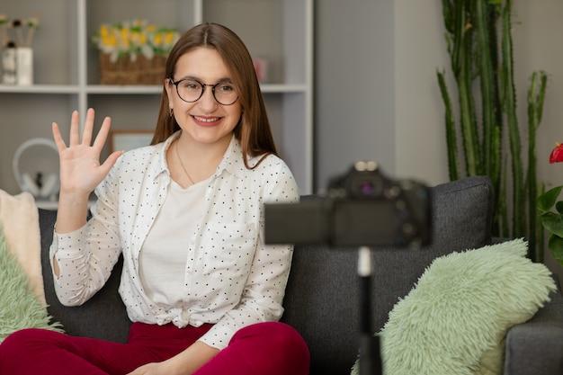 Feliz joven vlogger agitando la mano hablando mirando a la cámara web de la cámara, amigable chica comunicándose con un amigo en línea hacer una videollamada hablando grabar estilo de vida vlog distancia entrevista de trabajo