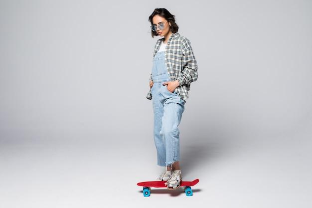 Feliz jovencita en longitud completa sosteniendo patineta mirando hacia el lado en el espacio de copia en blanco, aislado
