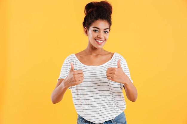 Feliz jovencita mostrando los pulgares hacia arriba y sonriendo aislado sobre amarillo