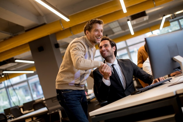 Feliz jóvenes empresarios apretón de manos junto a la mesa en la oficina
