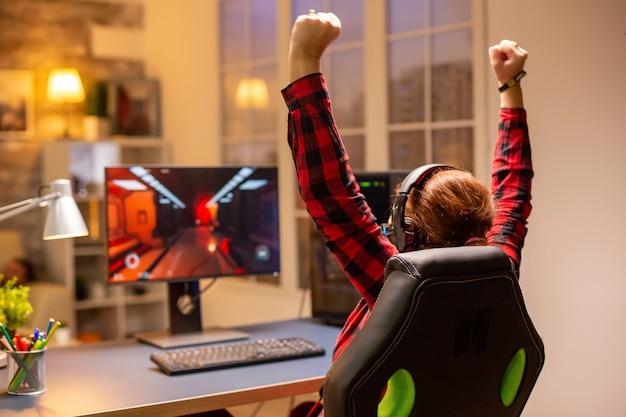 Feliz jugador emocionado ganando un videojuego en línea a altas horas de la noche en la sala de estar