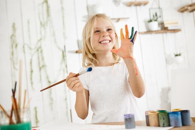 Feliz y juguetona linda chica rubia pecosa vestida de blanco, sosteniendo el pincel en una mano y mostrando la otra mano, que estropeó con pintura.