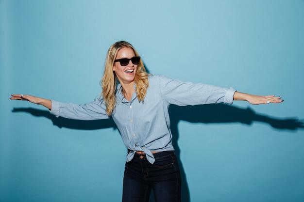 Feliz juguetona mujer rubia en camisa y gafas de sol mirando a otro lado