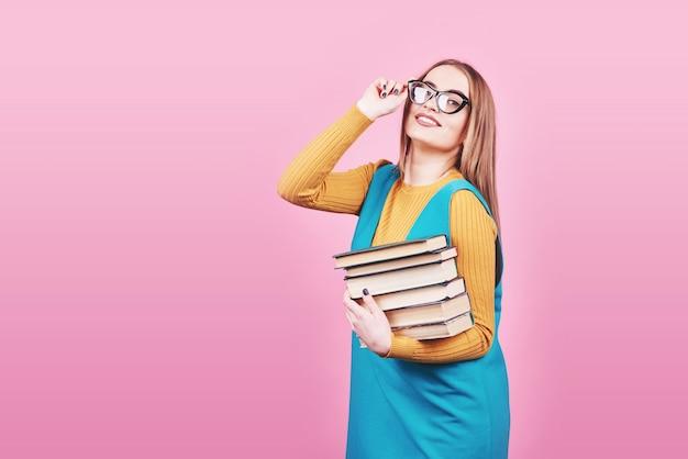 Feliz linda chica en gafas sosteniendo en las manos una pila de libros aislados en rosa colorido