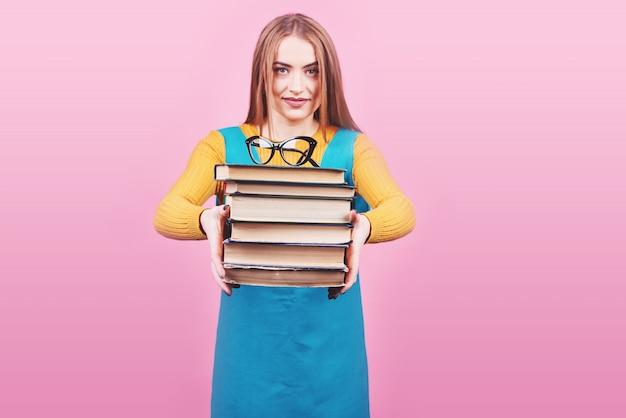 Feliz linda chica sosteniendo en las manos una pila de libros aislados en colorido rosa